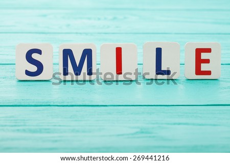Word smile on blue wooden background. Selective focus