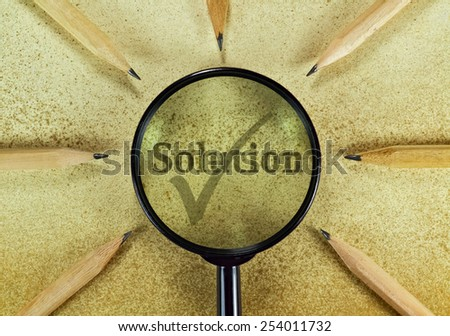 Word Solution under magnifying glass on vintage background - stock photo