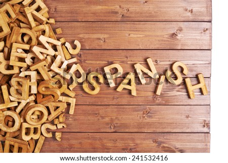 Word spanish made with block wooden letters next to a pile of other letters over the wooden board surface composition - stock photo