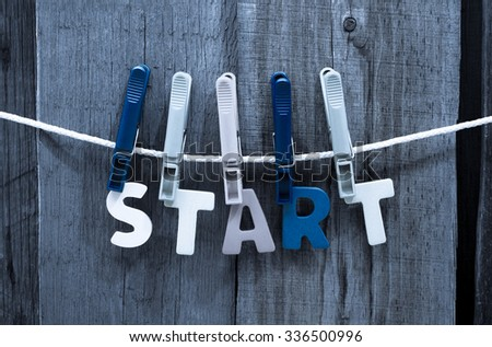 word start fasten clothespins on a rope behind a wooden background - stock photo
