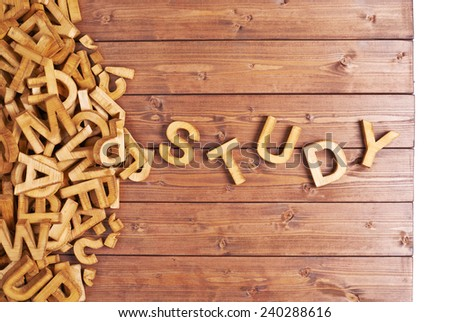 Word study made with block wooden letters next to a pile of other letters over the wooden board surface composition - stock photo