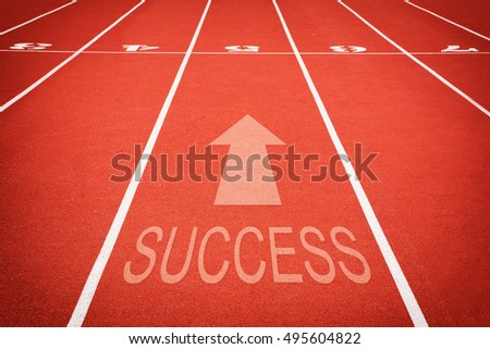 "word ""SUCCESS"" and athletic track number on red rubber racetrack, texture of runnin."