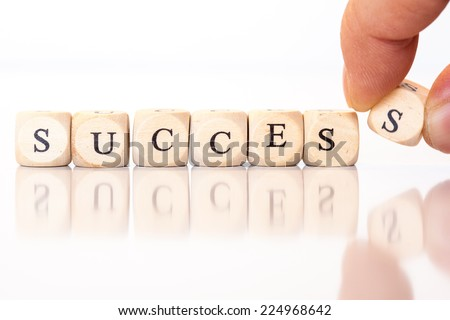Word Success spelled from single dice letters, with reflection on bottom, hand putting on the last letter. - stock photo