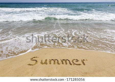 Word summer written in sand on the beach  - stock photo