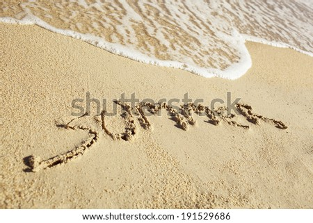 Word Summer written on a sandy beach