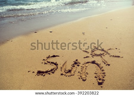 Word sun handwritten on  sand on the beach next to the water line
