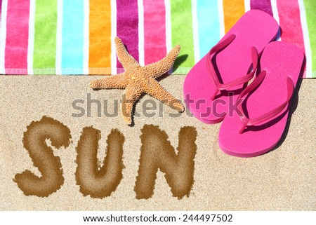 Word - Sun - on a tropical beach with a striped towel in the colors of the rainbow, pink slip slops and a sea star on sunny golden sand symbolic of travel and a summer vacation in the tropics - stock photo