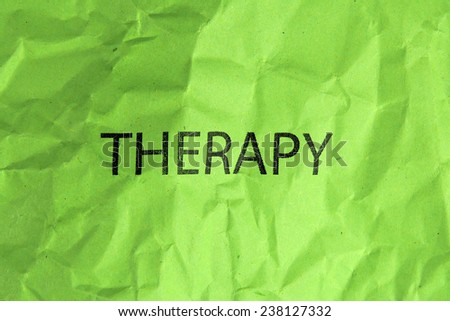 word therapy on crumpled green paper - stock photo