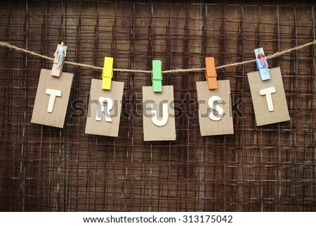 word trust design by white letterpress with box paper hang on rope by wooden peg over metal net and brown wooden background, vignette effect. - stock photo