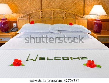 Word Welcome made of palm leafs and flowers on bed - stock photo