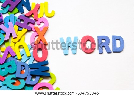 "Word "" Word "" is beside the group of English letters made by colorful wooden on white background. English language learning concept"