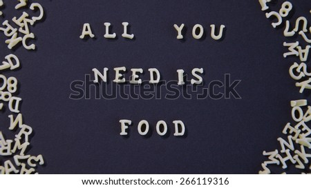 Words All You Need Is Food Written With Pasta Letters, on a black background - stock photo