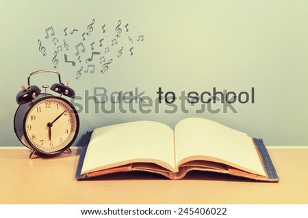 """words """"back to school""""  and alarm clock with note on table. - stock photo"""