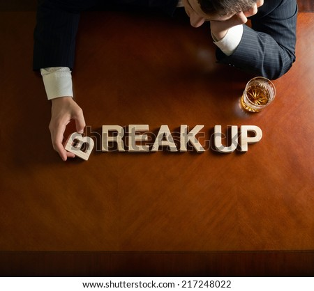 Words Break Up made of wooden block letters and devastated middle aged caucasian man in a black suit sitting at the table with the glass of whiskey, top view composition with dramatic lighting - stock photo