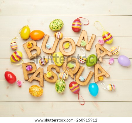 Words Buona Pasqua as Happy Easter in italian language made of wooden letters and surrounded with multiple egg decorations as a festive Easter background composition - stock photo