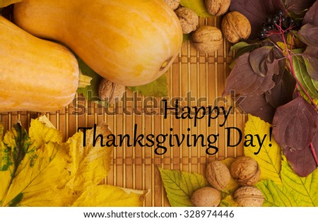 Words happy thanksgiving day on the rustic background with maple leaves, walnuts and two pumpkins