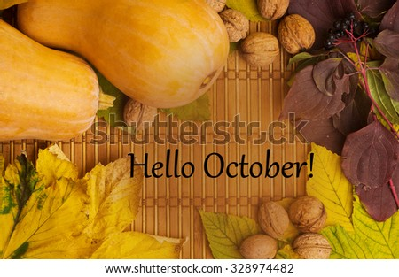 Words hello october on the rustic background with maple leaves, walnuts and two pumpkins