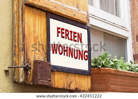 Words holiday apartment in German on old German wooden window with shutters background , close up
