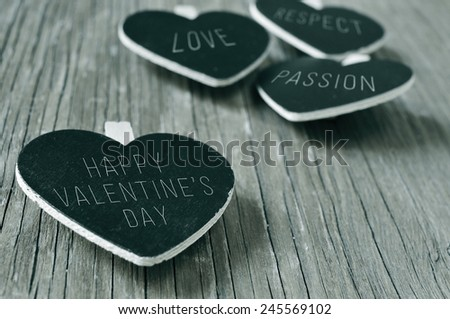 words love, respect and passion, and the sentence happy valentines day written in some heart-shaped chalkboards, on a rustic wooden surface, in black and white - stock photo