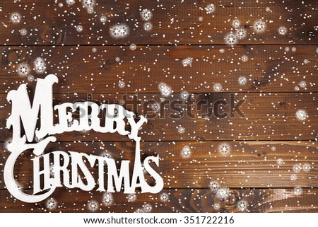Words Merry Christmas on old wooden table with snow and stars - stock photo