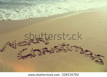 Words Merry Christmas written on a sandy beach, waves in the background - stock photo