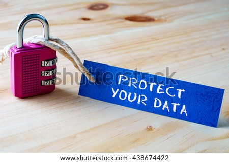 Words PROTECT YOUR DATA written on tag label tied with a padlock. - stock photo