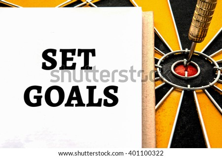 Words set goals with dart target arrow on the center of dartboard, Smart goal target success business investment financial strategy concept, abstract background - stock photo