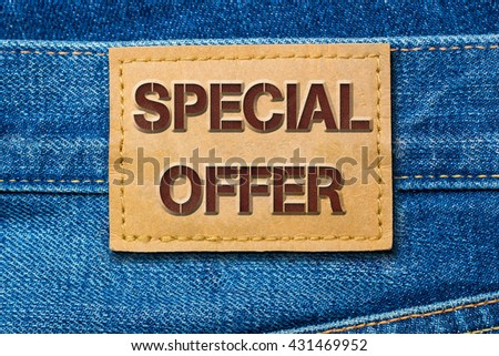 Words SPECIAL OFFER on denim blue jeans fashion leather label background, close up - stock photo