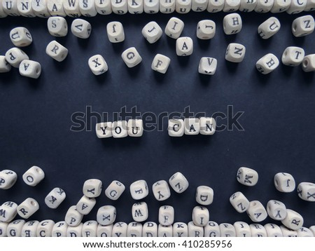 Words You can of small white cubes next to a bunch of other letters on the surface of the composition on a dark background