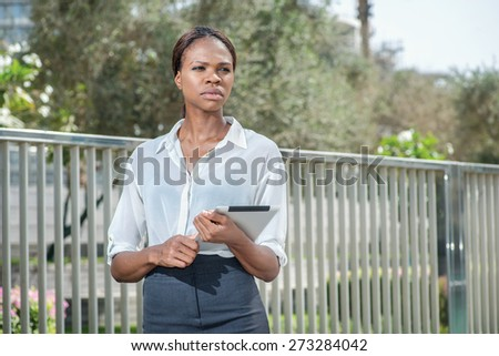 Work and business. African businesswoman businessman holding a tablet in her hand while standing on the street and looking to the side. Female dressed in formal attire - stock photo