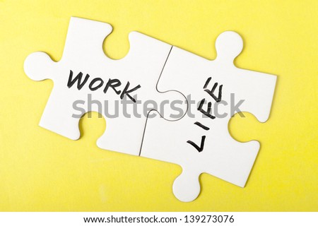 Work and life words written on two pieces of jigsaw puzzle - stock photo