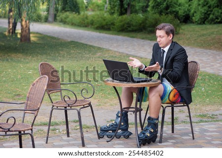 Work and relax. Businessman dressed in suit, shorts and rollers working with laptop at the outdoors cafe - stock photo