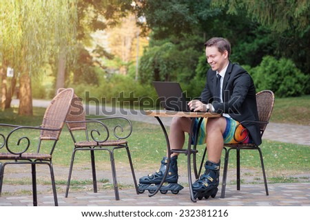 Work and relax.  smiling Businessman dressed in suit, shorts and rollers working with laptop at the park cafe outdoors - stock photo