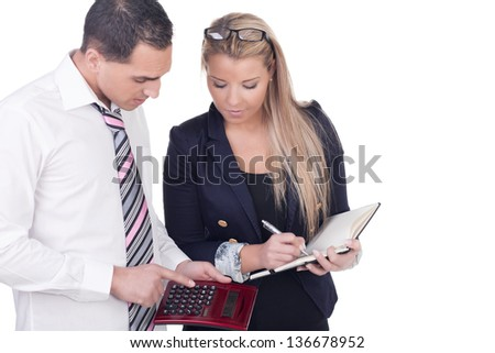 Work colleagues comparing figures with the man analysing the statistics on a calculator while the woman looks on waiting to write the information in a notebook, upper body studio portrait on white - stock photo