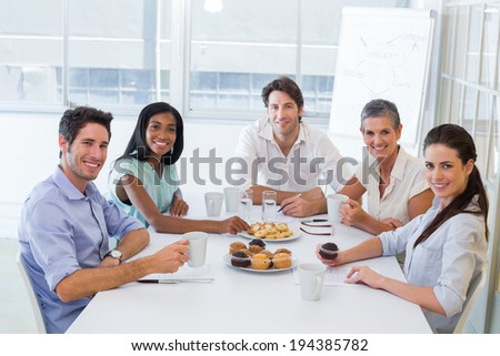 Work colleagues having hot beverages and muffins and smiling at the camera in the office - stock photo
