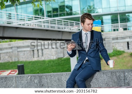 Work does not sleep! Successful businessman sitting on the parapet of the tablet and drinking coffee