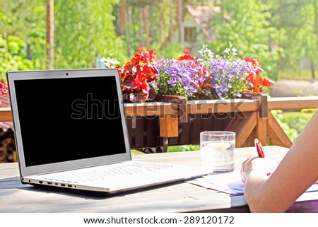 work from home, table with laptop on terrace - stock photo