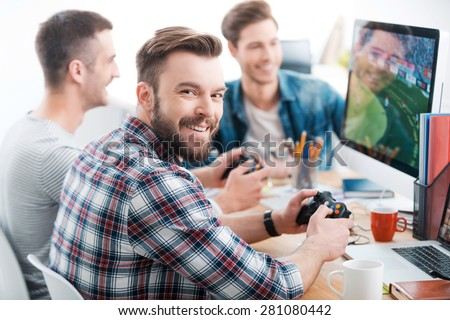 Work hard play hard. Three young men playing computer games while sitting at the desk in the office - stock photo