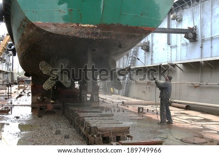 Work in dry dock with water jet cleans the bottom of the ship from sea vegetation and mussel colonies during routine overhaul on outdated manual technology - stock photo