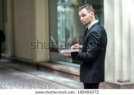 Work in full swing. Successful businessman standing in the street holding a laptop and working outdoors.
