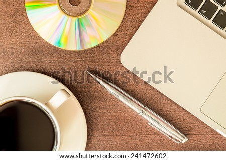 Work in the office, coffee cup and a plate with an optical disk with laptop on the wooden table. In yellow tone - stock photo