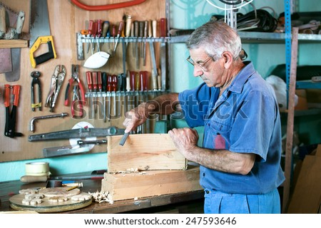 work of a carpenter sanding a piece of wood in the workshop of his house / cabinetmaker filing in the bench in garage at home - stock photo