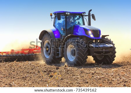 Work of a tractor on a wheat field on a sunny day. Field of tractor plowing.