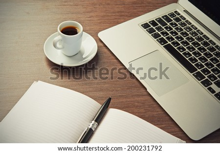 work office desk with a cup of coffee computer laptop, notebook, pen - stock photo
