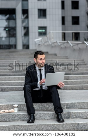 Work outside the office. Successful young man sitting and working on a laptop. Businessman sitting on the stairs