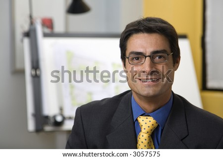 work place: successful businessman smiling and staring at the camera - stock photo