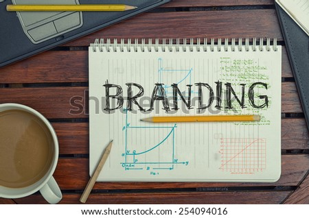 work place with notebook with note about: Branding with laptop and coffee on table - stock photo