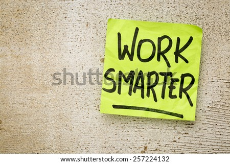 work smarter reminder on a green sticky note against rustic barn wood p productivity concept - stock photo