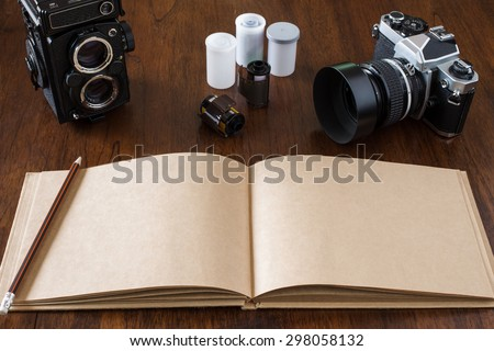 Work space for photographer, designer or hipster style. Have a  film camera, film, book, pencil on wooden table. - stock photo
