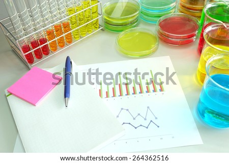 work table in laboratory and colorful fluid in glassware